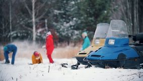 Familia del bosque del invierno en la ropa colorida que juega bolas de nieve en la cámara lenta Motos de nieve en el primero plan metrajes
