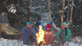 Familia del bosque del invierno que se sienta en el bosque por el fuego y que fríe las salchichas metrajes