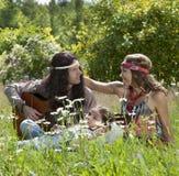 Familia del hippie que toca la guitarra en el campo Imagen de archivo libre de regalías