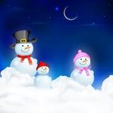 Familia del muñeco de nieve en noche de la Navidad Fotos de archivo