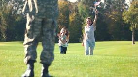 Familia del ` s del soldado que corre con los fondos de los E.E.U.U. almacen de metraje de vídeo