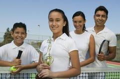 Familia del tenis en corte por la hija neta que sostiene el retrato del trofeo Imagen de archivo libre de regalías