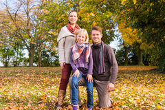 Familia delante de árboles coloridos en otoño o caída Fotos de archivo