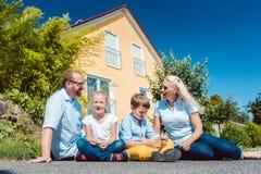 Familia delante de su hogar fotos de archivo