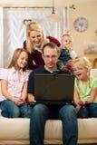 Familia delante del ordenador que tiene conferenc video Imagenes de archivo