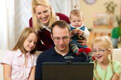 Familia delante del ordenador que tiene conferenc video Imágenes de archivo libres de regalías