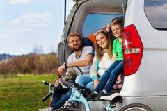 Familia deportiva feliz que se sienta en la bota del coche imagen de archivo libre de regalías
