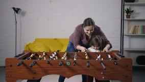 Familia despreocupada feliz que juega a fútbol de la tabla en casa almacen de video