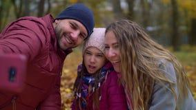 Familia despreocupada que hace la foto del selfie en naturaleza del otoño metrajes