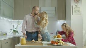 Familia despreocupada que prepara el desayuno en la cocina metrajes