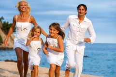 Familia dinámica que corre en la playa. Imagen de archivo