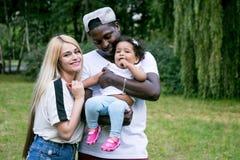 Familia diversa feliz con la hija en el parque El papá y la mamá detienen a su hija foto de archivo