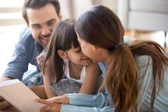 Familia diversa que miente en el piso caliente que lee un cuento de hadas del libro imágenes de archivo libres de regalías