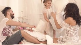 Familia divertida feliz que tiene una lucha de almohada en cama almacen de video