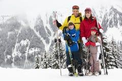 Familia el día de fiesta del esquí en montañas Imagenes de archivo