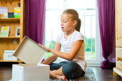 Familia - el niño o el adolescente abre un regalo Fotos de archivo libres de regalías
