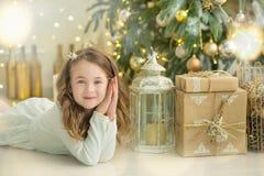Familia el Nochebuena en la chimenea Niños que abren presentes de Navidad Niños debajo del árbol de navidad con las cajas de rega Foto de archivo libre de regalías