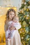 Familia el Nochebuena en la chimenea Niños que abren presentes de Navidad Niños debajo del árbol de navidad con las cajas de rega Fotos de archivo