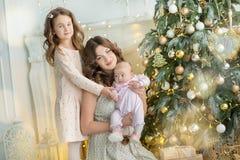 Familia el Nochebuena en la chimenea Niños que abren presentes de Navidad Niños debajo del árbol de navidad con las cajas de rega Imagen de archivo