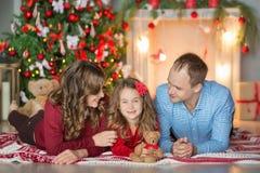 Familia el Nochebuena en la chimenea Niños que abren presentes de Navidad Niños debajo del árbol de navidad con las cajas de rega Fotografía de archivo