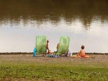 Familia: el padre, la madre y el hijo están descansando sobre sillas de playa en la orilla al lado de la charca Día de fiesta de  foto de archivo