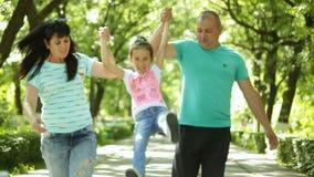 Familia El papá y la mamá detienen a su hija, ellos caminan en el parque La risa está sonriendo almacen de video
