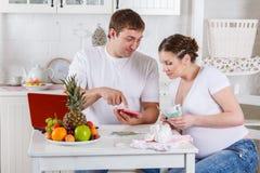 Familia embarazada con el dinero. Presupuesto familiar. Fotos de archivo