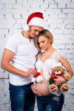 Familia embarazada de los jóvenes con un oso del sombrero de Papá Noel del Año Nuevo y de peluche de la Navidad Imagen de archivo