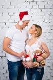 Familia embarazada de los jóvenes con un oso del sombrero de Papá Noel del Año Nuevo y de peluche de la Navidad Imagen de archivo libre de regalías