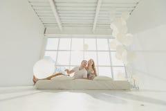 Familia embarazada feliz con un pequeño hijo, jugando contra la ventana en un cuarto blanco Fotografía de archivo