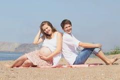 Familia embarazada joven feliz en el mar Fotografía de archivo libre de regalías