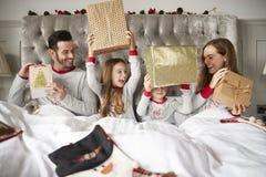 Familia emocionada en la cama en casa que abre los regalos el día de la Navidad fotografía de archivo libre de regalías