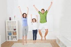 Familia emocionada en la ropa de deportes que salta en casa Fotos de archivo