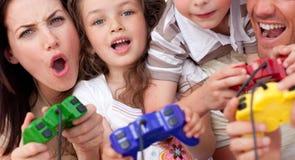 Familia emocionada que juega a los juegos video Foto de archivo libre de regalías
