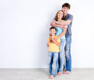 Familia en abrazo cerca de la pared Foto de archivo