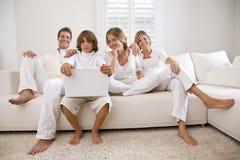 Familia en blanco en el sofá blanco Fotos de archivo libres de regalías