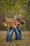Familia en bosque del otoño con los pulgares para arriba Imagenes de archivo