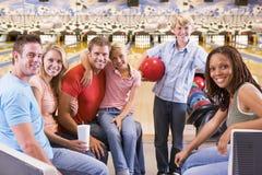 Familia en callejón de bowling con la sonrisa de dos amigos Imagenes de archivo