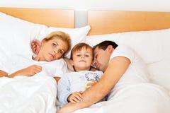 Familia en cama imagen de archivo