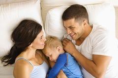 Familia en cama. Fotos de archivo
