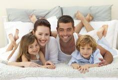 Familia en cama que sonríe en la cámara Foto de archivo libre de regalías