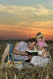 Familia en campo en puesta del sol Fotografía de archivo