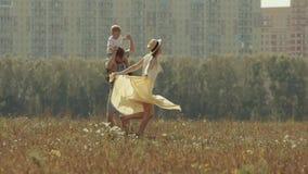 Familia en campo que disfruta de su fin de semana Giran y corren alrededor para tener un buen rato almacen de metraje de vídeo