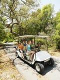 Familia en carro de golf. Foto de archivo