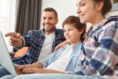 Familia en casa que se sienta en el sofá en la sala de estar junto que lee el blog en Internet en el primer feliz del ordenador p foto de archivo