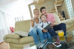 Familia en casa usando la tableta Foto de archivo libre de regalías