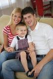 Familia en casa usando la tableta Imágenes de archivo libres de regalías