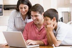 Familia en cocina con la sonrisa de la computadora portátil Foto de archivo libre de regalías