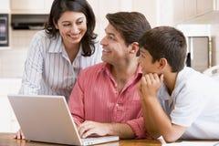 Familia en cocina con la sonrisa de la computadora portátil Fotos de archivo libres de regalías