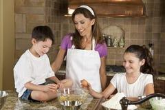 Familia en cocina que cocina y que cuece al horno Fotos de archivo